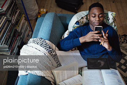 High angle view of teenage boy using mobile phone while lying on sofa with books at home - p426m2101609 by Maskot