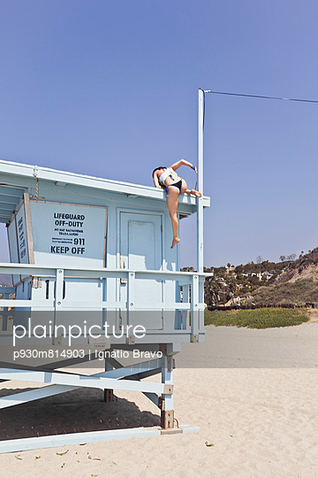 Woman climbing up a lifeguard tower - p930m814903 by Phillip Gätz