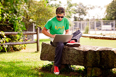 Man using laptop computer while sitting on rock at park - p1166m985487f by Cavan Images