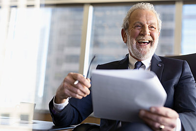 Laughing senior male lawyer reviewing paperwork in meeting - p1192m1213062 by Hero Images