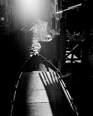 Kanal in Venedig bei Gegenlicht mit venezianischer Flagge - p1493m1585676 von Alexander Mertsch