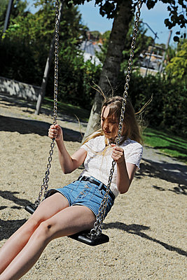 Teenage girl on a swing  - p1540m2122854 by Marie Tercafs