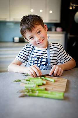 7 year old boy cuts green asparagus and potatoes in modern kitchen, lower Austria - p300m2180723 von Epiximages