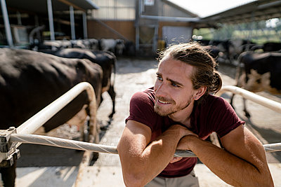 Smiling young farmer at cow house on a farm - p300m2206810 by Kniel Synnatzschke