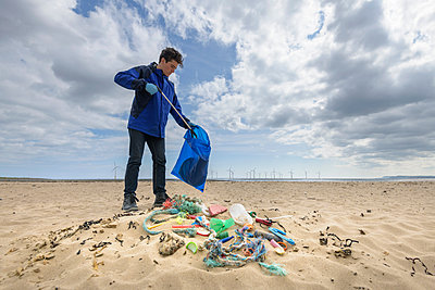 Man picking up plastic pollution collected on beach, North East England, UK - p429m2004548 by Monty Rakusen