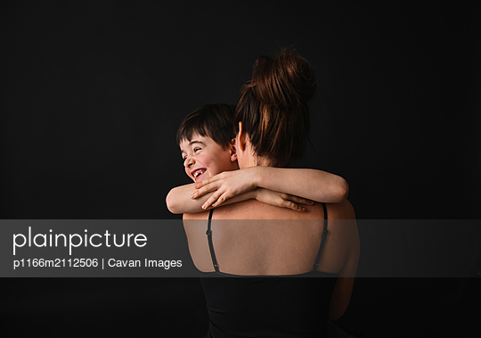 Portrait of young boy hugging mother against black background. - p1166m2112506 by Cavan Images
