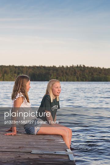 two girls on a jetty - p1323m1582727 von Sarah Toure