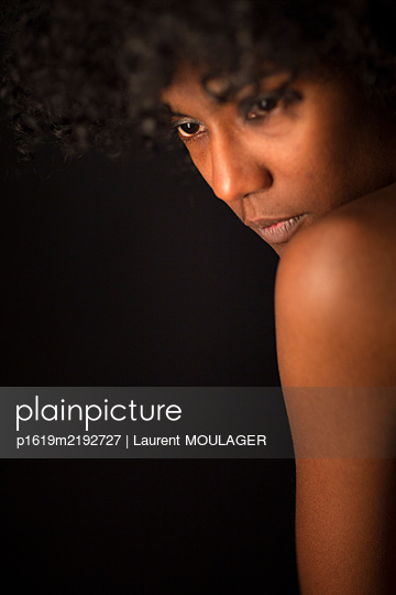 Portrait of a young black woman looking down  - p1619m2192727 by Laurent MOULAGER