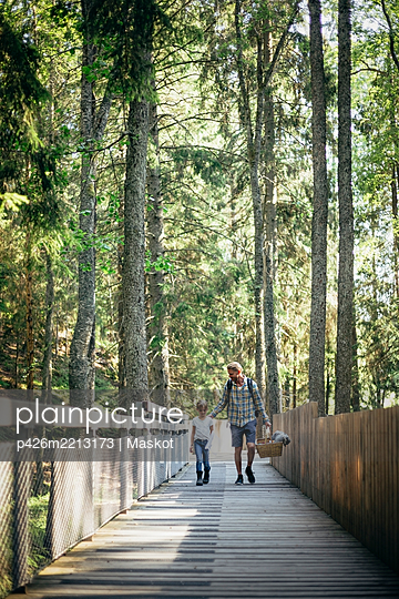 Father talking to daughter while walking on footbridge in forest - p426m2213173 by Maskot