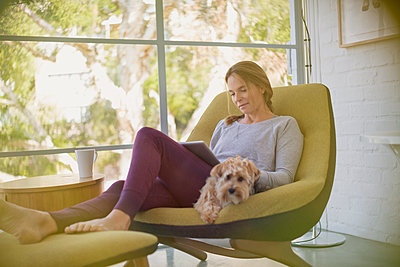 Woman with dog relaxing, using digital tablet in chair - p1023m1406918 by Tom Merton