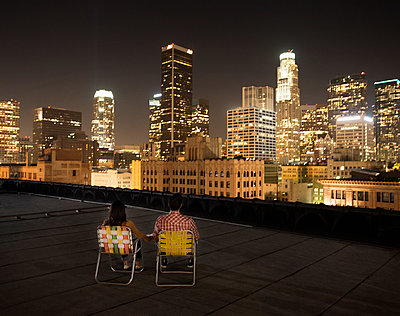 A couple on a rooftop overlooking Los Angeles at night, sitting side by side looking over the city.  - p1100m1107173 by Mint Images