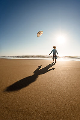 Toddler boy playing Frisbee on a sunny day at the beach - p1166m2108127 by Cavan Images