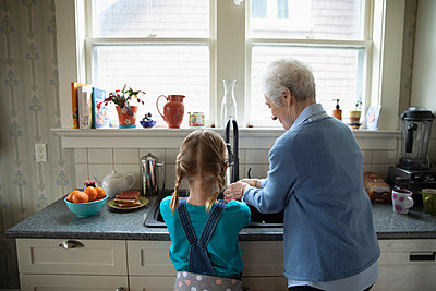 Grandmother and granddaughter at kitchen sink - p1192m1583431 by Hero Images