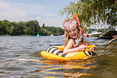 Little girl with swimming ring in lake - p1394m1440846 by benjamin tafel