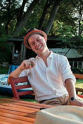 Junger Mann raucht eine Zigarre im Freien - p1437m2008213 von Achim Bunz