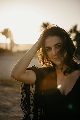 Beautiful woman with hand in hair on beach during sunset - p300m2256161 by letizia haessig photography