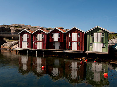 Fishing huts reflecting in harbor - p575m718481f by Benny Karlsson