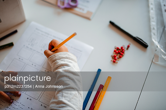High angle view of girl doing homework - p312m2237254 by Anna Johnsson