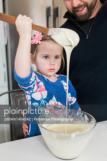 Girl with father gazing at wooden spoon drizzle at kitchen counter - p924m1404242 by Rosenlee Photography