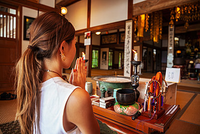 Two Japanese women kneeling in Buddhist temple, praying. - p1100m2146575 by Mint Images