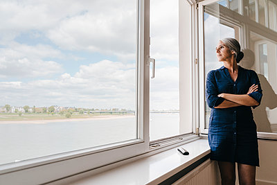 Businesswoman looking out of window in waterfront office - p300m1469974 by Kniel Synnatzschke