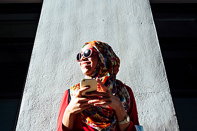 Smiling woman in hijab looking away while holding mobile phone against concrete column - p300m2240721 by Jose Luis CARRASCOSA