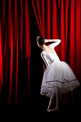 A ballet dancer peeking through a stage curtain, rear view - p30110688f by Iris Friedrich