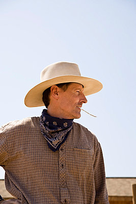 Profile of a cowboy chewing on a piece of straw - p3018462f by Adam Burn