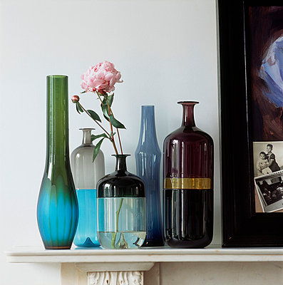 Row of coloured glass vases and bottles on a mantelpiece - p349m770206 by Jan Baldwin
