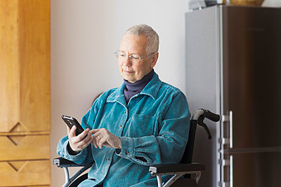 Senior woman sitting in a wheelchair, using mobile phone. - p429m2165077 by Sigrid Gombert