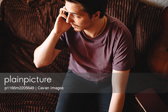 Young man talking on mobile phone sitting on sofa at home - p1166m2205649 by Cavan Images