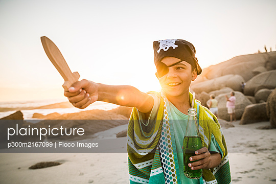 Boy dressed up as pirat on the beach at sunset - p300m2167099 by Floco Images