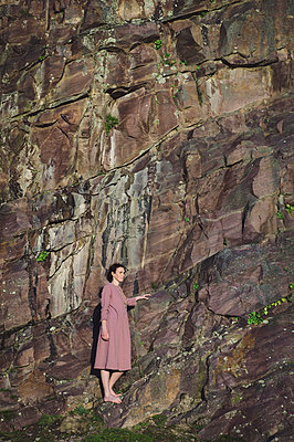France, Brittany, Woman in a pink dress at the bottom of the pink cliff - p1150m2264254 by Elise Ortiou Campion