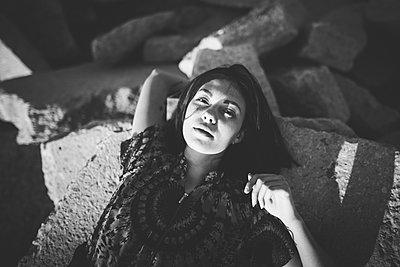 Young woman lying on rocks - p1427m2169355 by Oleksii Karamanov