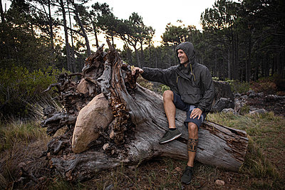 Hiker marvels at giant tree root - p1640m2261052 by Holly & John