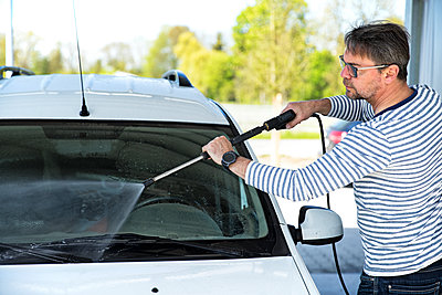 Man cleaning windscreen of his car - p300m1460362 by Roman Märzinger