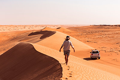 Man walking on a sand dune, Wahiba Sands, Oman - p300m2104060 by Valentin Weinhäupl