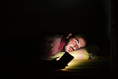 Man lying in bed using smartphone at night - p300m2199664 by Xavier Lorenzo