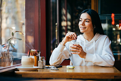 Thoughtful woman with straw drinking coffee at cafe - p300m2282461 by alev