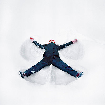 High angle view of a young woman making a snow angel - p3740739 by Lauri Rotko