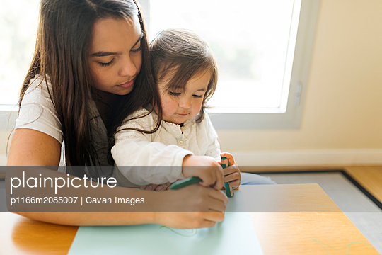 Young nanny with a toddler making drawing with colored pencils - p1166m2085007 by Cavan Images