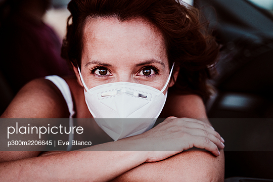 Woman wearing face mask in car during COVID-19 - p300m2206645 by Eva Blanco