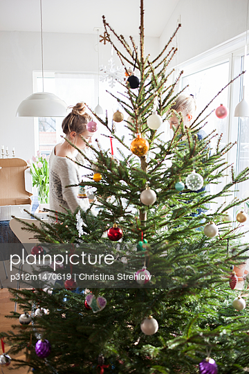 Girl decorating Christmas tree - p312m1470619 by Christina Strehlow
