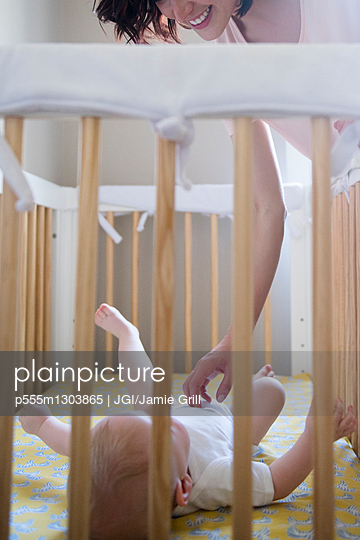 Caucasian mother tickling belly of baby son in crib - p555m1303865 by JGI/Jamie Grill
