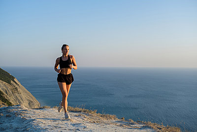 Athletic young woman is running on mountain near sea - p1363m2013493 by Valery Skurydin