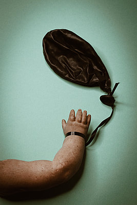 Doll hand with deflated balloon - p1623m2222159 by Donatella Loi