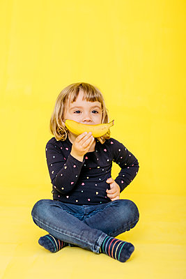 Full length of preschool girl holding banana while sitting with cross-legged and looking away against colored background - p300m2198445 by Josep Rovirosa