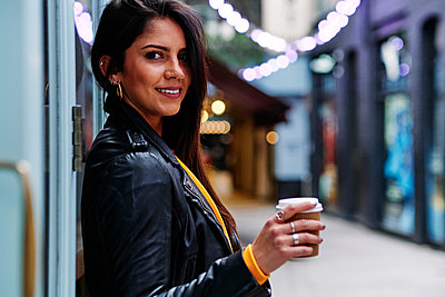 Beautiful woman standing with disposable coffee cup in city - p300m2273657 by Angel Santana Garcia