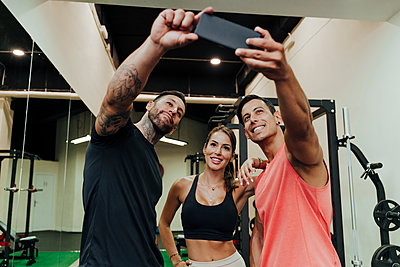 Smiling friends taking selfie through mobile phone at gym - p300m2274515 by Eva Blanco