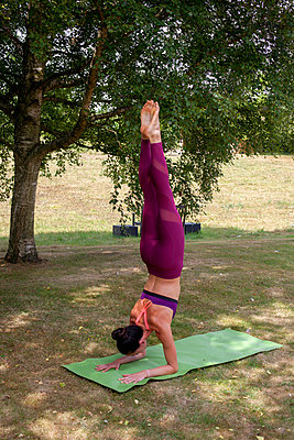 Woman practicing yoga in garden, forearm stand - p429m2032212 by Image Source